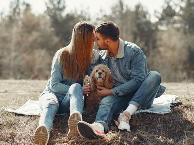 couple en train de s'embrasser à côté de leur chien