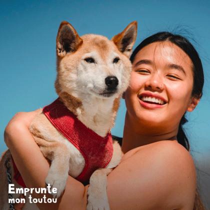 femme souriante portant un chien de race shiba inu dans ses bras