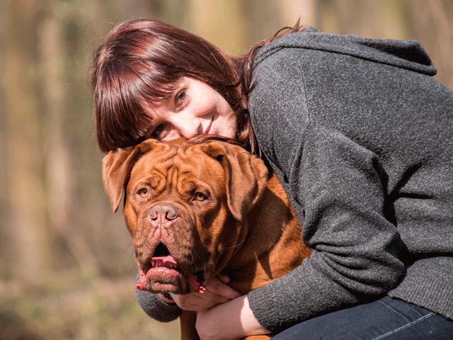 femme serrant un dogue de bordeaux dans ses bras